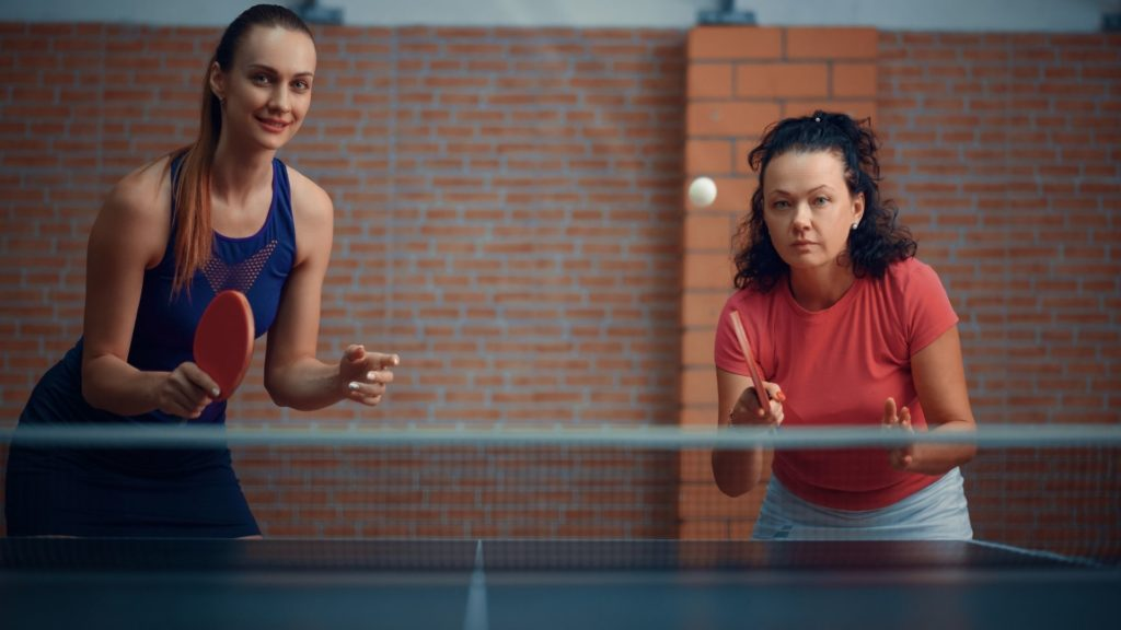Picture of women playing ping pong doubles while learning ping pong rules.